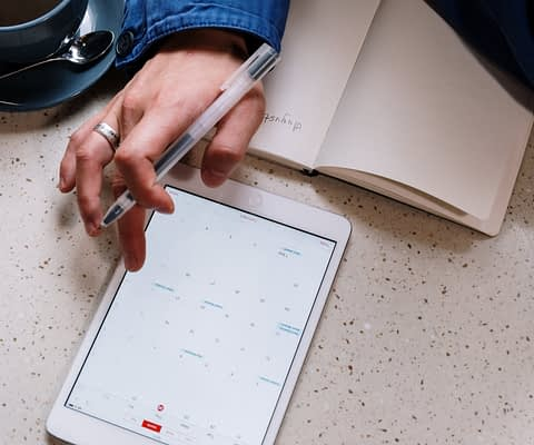 person holding pen and using a tablet
