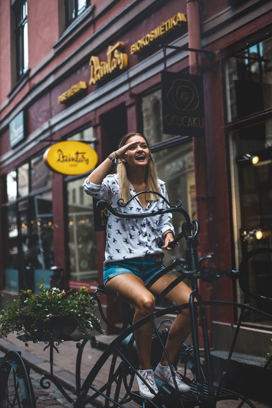 shallow focus photography of smiling woman riding a bicycle
