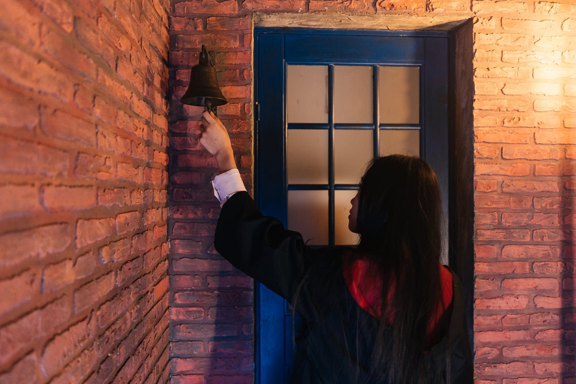 person by the door holding bell s clapper