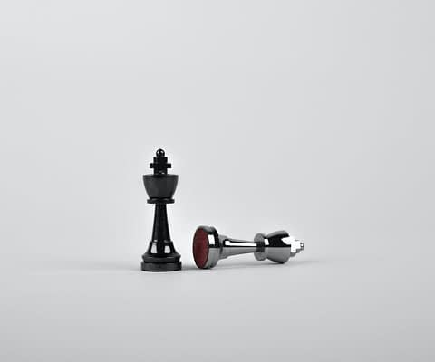 two silver chess pieces on white surface