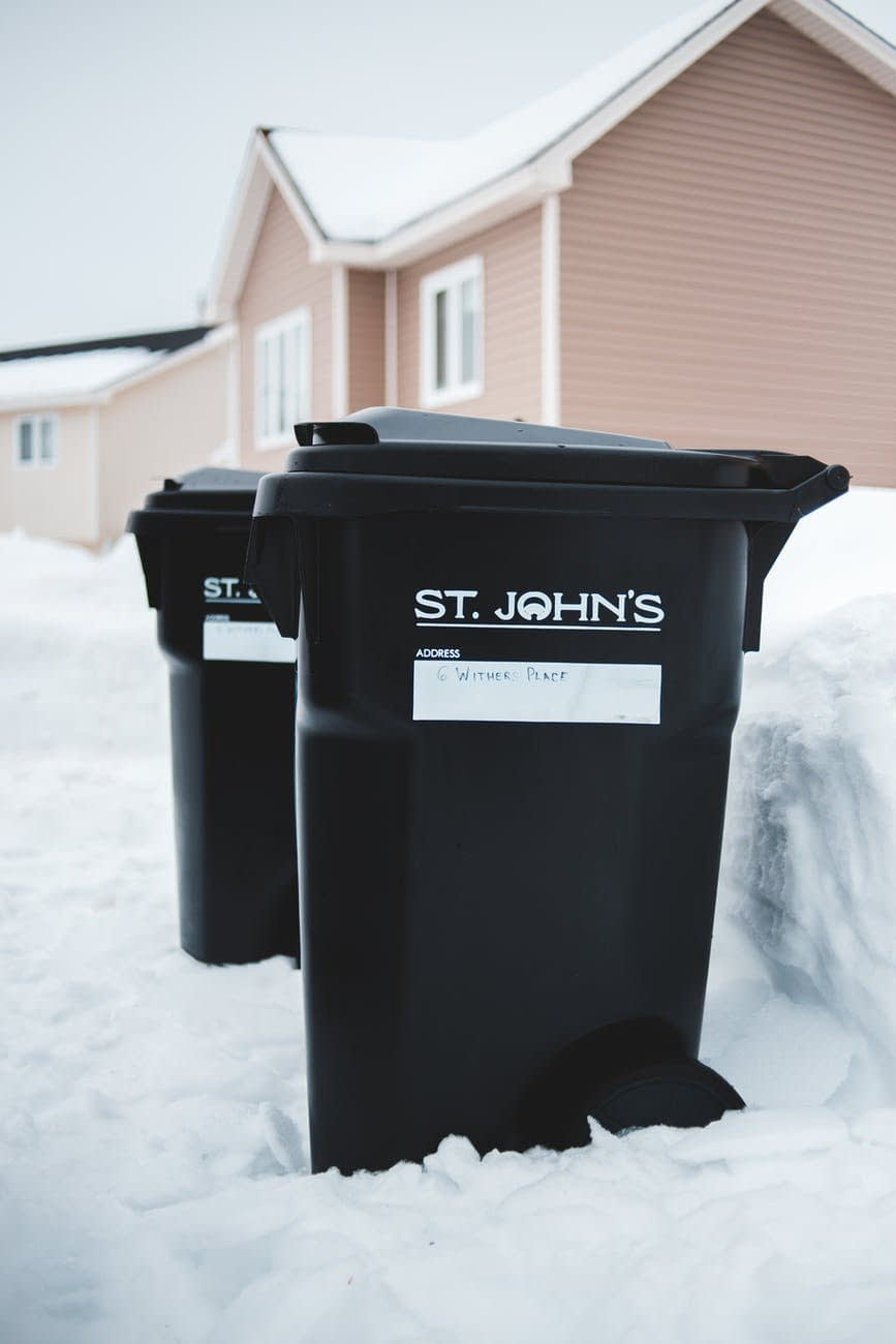 similar rubbish bins on snow near house facade in town